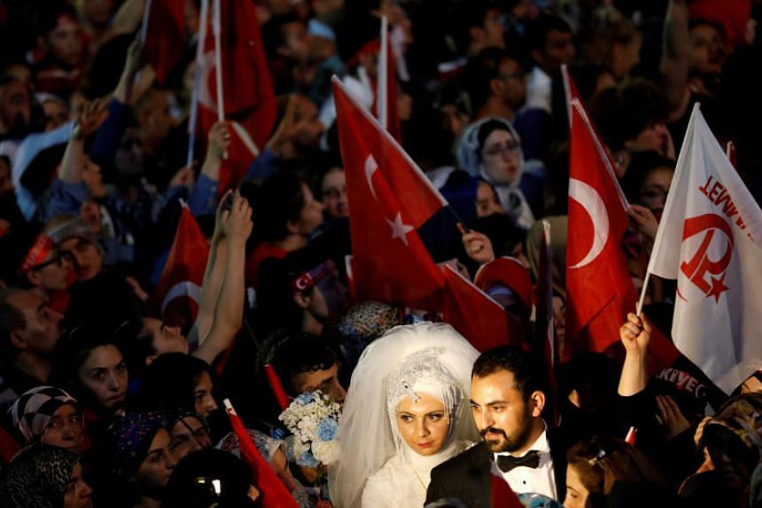 A bride and a groom attend a ceremony marking the first anniversary of the attempted coup in front of the Turkish Parliament in Ankara, Turkey on July 16, 2017.