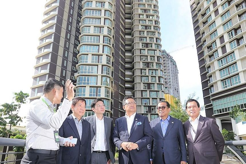 Touring the Afiniti Medini mixed-use development in Iskandar Puteri yesterday were (from second left) ministers Khaw Boon Wan and Lawrence Wong, with Malaysia's Minister in the Prime Minister's Department Abdul Rahman Dahlan, Johor Menteri Besar Moha