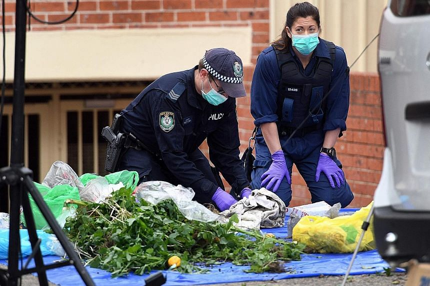 Police searching for evidence at a block of flats in the Sydney suburb of Lakemba yesterday. They found a flight number for a Jakarta to Sydney flight in a bin, but it was not clear if this flight was being targeted.