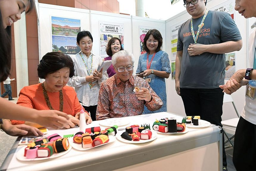 "President Tony Tan Keng Yam and his wife Mary rolling and appreciating decorative ""sushi"" at the Institute of Mental Health booth at Singapore Press Holdings' (SPH) Chinese Media Group charity event in support of the President's Challenge 2017. SPH h"