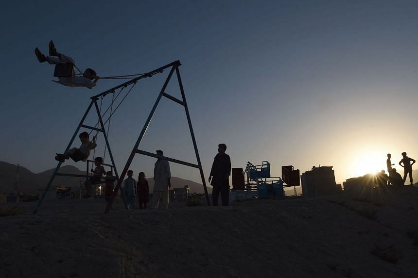Afghan children play on a swing during sunset on the outskirts of Kabul, on July 21, 2017.