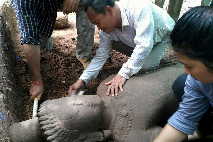 This handout photo taken on July 30, 2017 and released on August 1, 2017 by the Apsara Authority - the state agency charged with managing the Angkor temple complex - shows archaeologists excavating a statue from the ground at the complex in Siem Reap