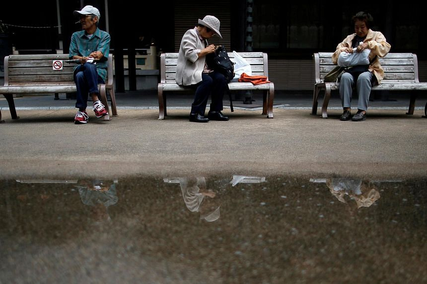 People take a break on bench seats at Tokyo's Sugamo district, an area popular among the Japanese elderly, in Tokyo, on Aug 29, 2014.