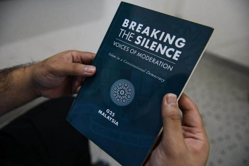 In this photo illustration taken in Kuala Lumpur on Aug 1, 2017, a man holds the book Breaking The Silence: Voices Of Moderation - Islam In A Constitutional Democracy.