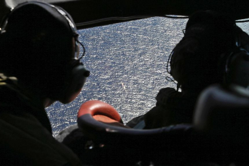 Crew members looking out the cockpit windows of a RNZAF P3 Orion during search operations for the wreckage and debris of missing Malaysia Airlines Flight MH370 in the southern Indian Ocean.