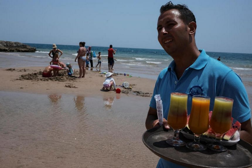Tourists relax on the beach as a hotel staff member sells cocktails in the Red Sea resort of Hurghad on July 21, 2017.