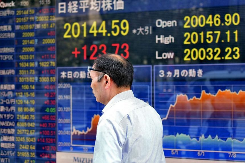 A man walks past a stock quotation board flashing the Nikkei 225 key index of the Tokyo Stock Exchange.