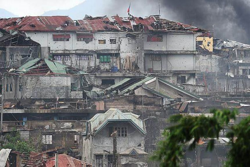 Black smoke billowing from a burning house after an an aerial strike by Philippine airforce attack helicopters targeting Islamist militants in Marawi, on July 22, 2017.