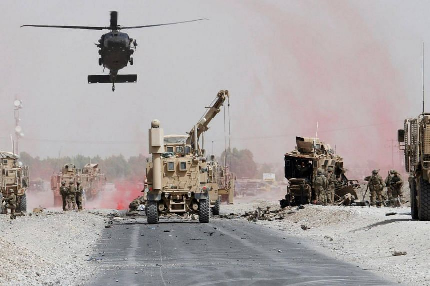 US troops assess the damage to an armoured vehicle of NATO-led military coalition after a suicide bomber's attack in Kandahar province, Afghanistan, on Aug 2, 2017.