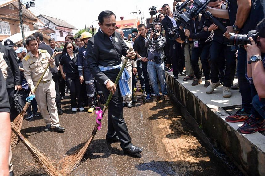 Thailand's Prime Minister Prayut Chan-O-Cha using a ceremonial broom to help clean a street in a town in the province of Sakon Nakhon in northeastern Thailand, after it was hit by floods.