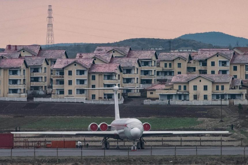 An Air Koryo aircraft as it sits parked in front of houses outside Pyongyang airport, on April 17, 2017.