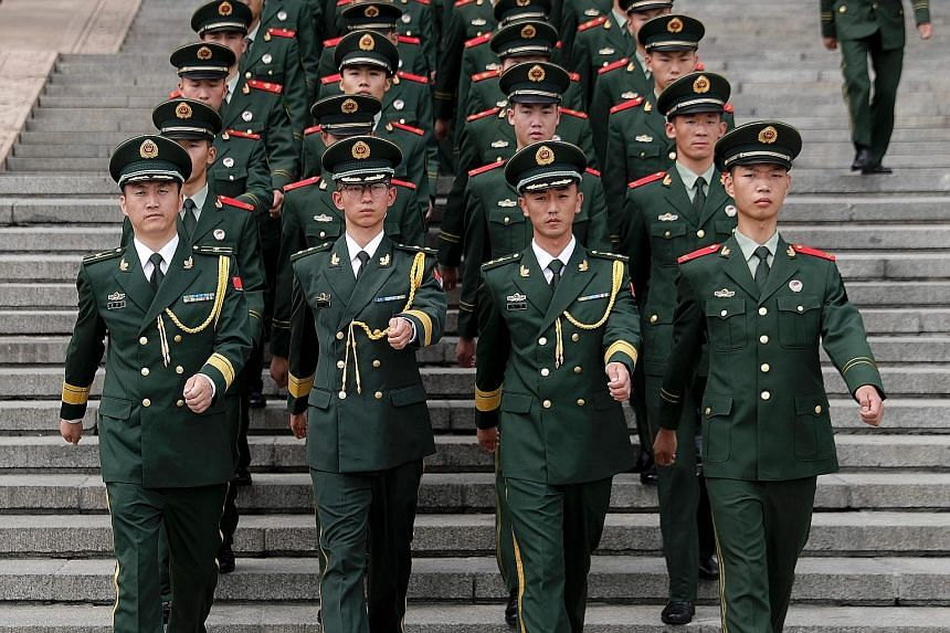 Chinese paramilitary policemen outside the Great Hall of the People after commemorating the 90th anniversary of the PLA yesterday.