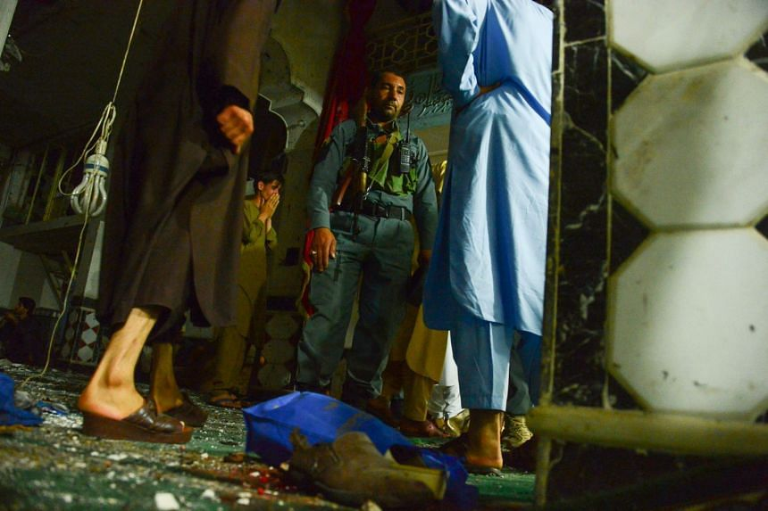 An Afghan security official inspects the site of a suicide bombing at a Shi'ite mosque in Herat on Aug 1, 2017.