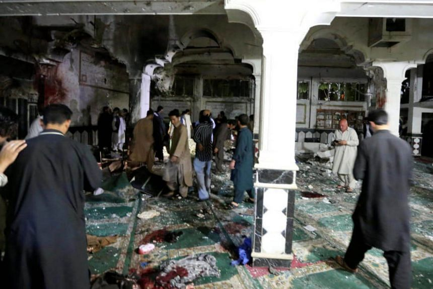 Afghan policemen and relatives inspect at the site of a suicide attack in Herat, on Aug 1, 2017.