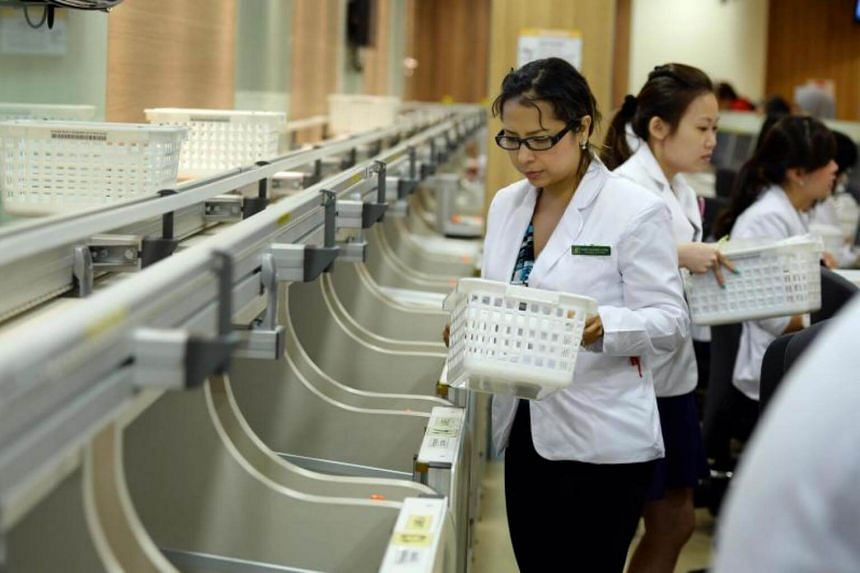 Pharmacy technicians picking up baskets containing medication for patients at the front counter at the SGH outpatient pharmacy.