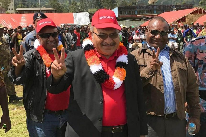 Papua New Guinea Prime Minister Peter O'Neill (centre) gesturing as he thanks voters during a visit to the town of Mendi.