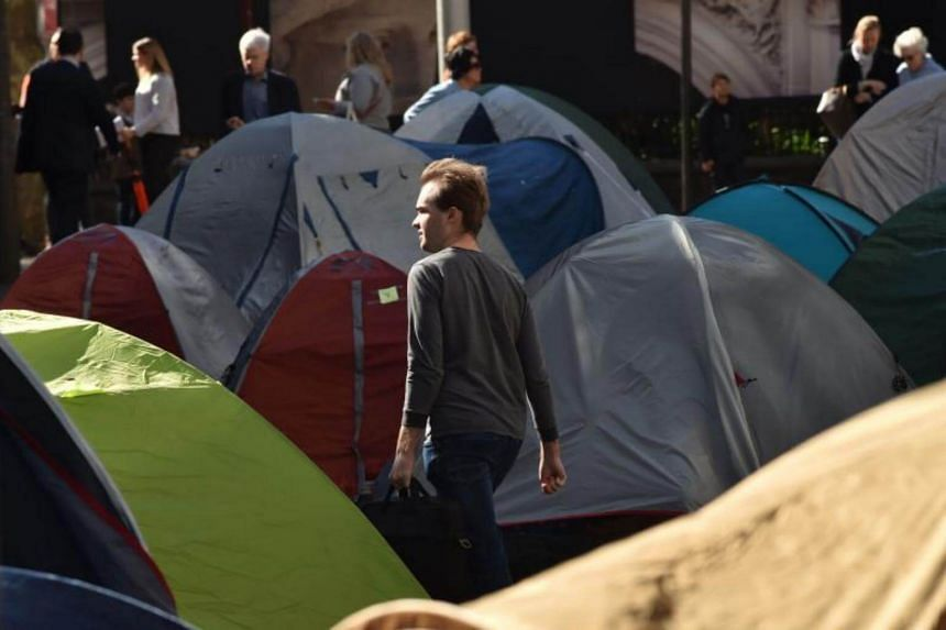 """A commuter passes between tents set up in Martin Place, which has become known as """"Tent City"""", in Sydney on Aug 2, 2017."""