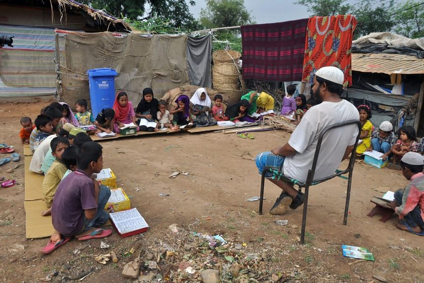 Rohingya Muslim refugee children from Myanmar study at a makeshift madrasa (religious school) on World Refugee Day in the outskirts of the Indian city Jammu.