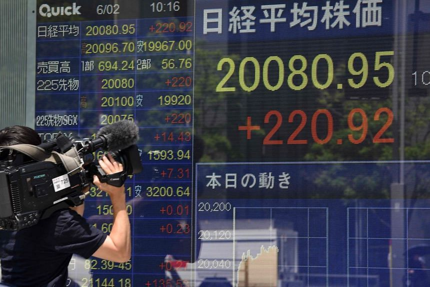 A television cameraman takes video images in front of a stock quotation board flashing the key Nikkei index of the Tokyo Stock Exchange.