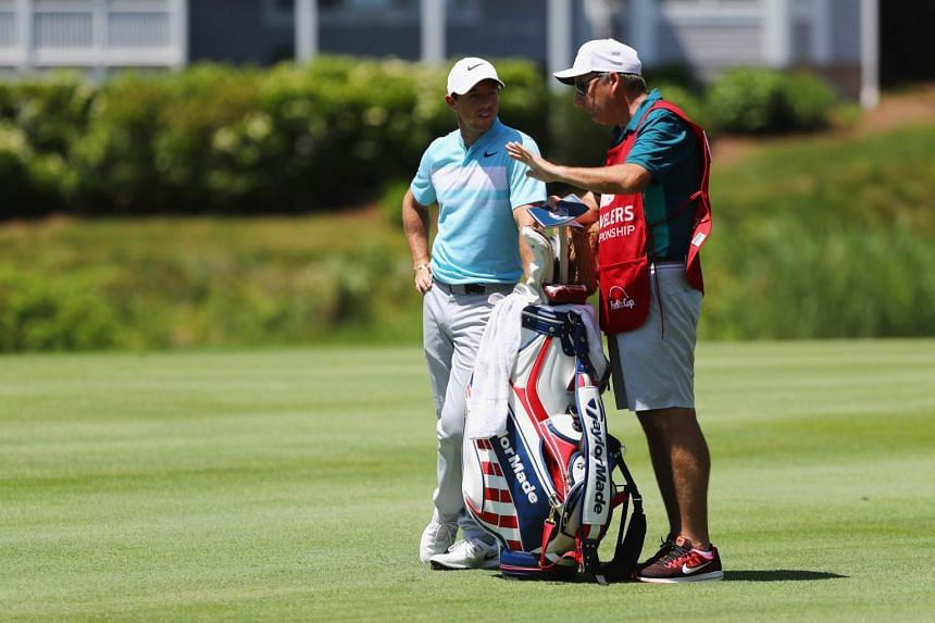 Rory McIlroy of Northern Ireland stands with caddie John-Paul Fitzgerald on the 13th hole during the third round of the Travelers Championship.