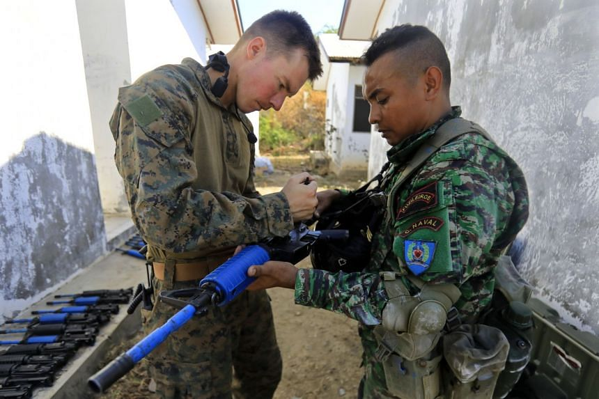 A US Marine (left) helps train an East Timor Navy personnel member during an exercise in Timor Leste, Aug 3, 2017.