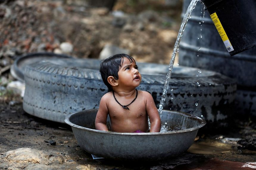 A baby girl is cooled by her mother on a hot summer day in Ahmedabad, India, May 2, 2017.