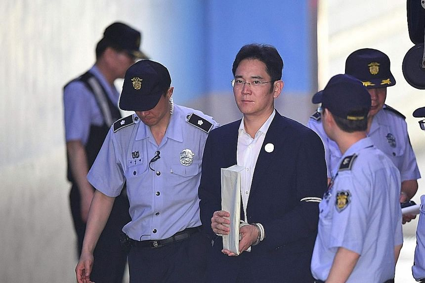 Samsung Electronics vice-chairman Lee Jae Yong being escorted by guards as he arrived at the Seoul Central District Court in Seoul yesterday.