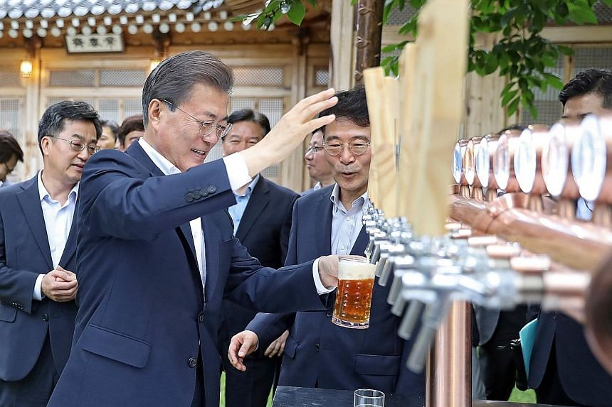 Mr Moon Jae In pouring himself a glass of beer during a meeting with business leaders in Seoul last week. His policy of listening to the people has helped him maintain a high approval rating. A recent poll showed 74 per cent approved of his managemen