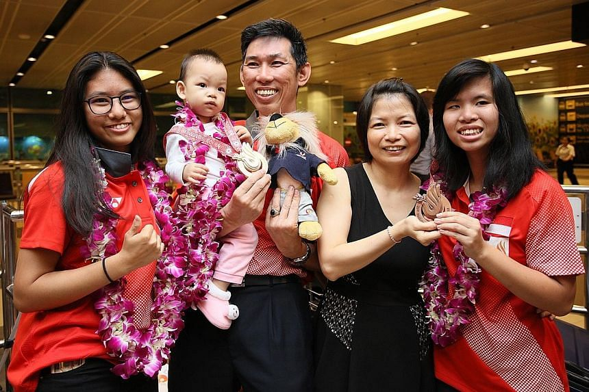 Gold medallist Adelia Naomi Yokoyama (left) and bronze medallist Kimberly Quek (right) pose for a photo with their coach Liew Foo Wai and his family after arriving at Changi Airport yesterday. National bowlers Yokoyama and Quek, who won Singapore's f