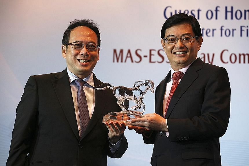 Finance Minister Heng Swee Keat receiving a token from Economic Society of Singapore president Euston Quah to signify his acceptance of the Honorary Fellow post yesterday during its annual dinner at Mandarin Orchard Singapore. Only five other people