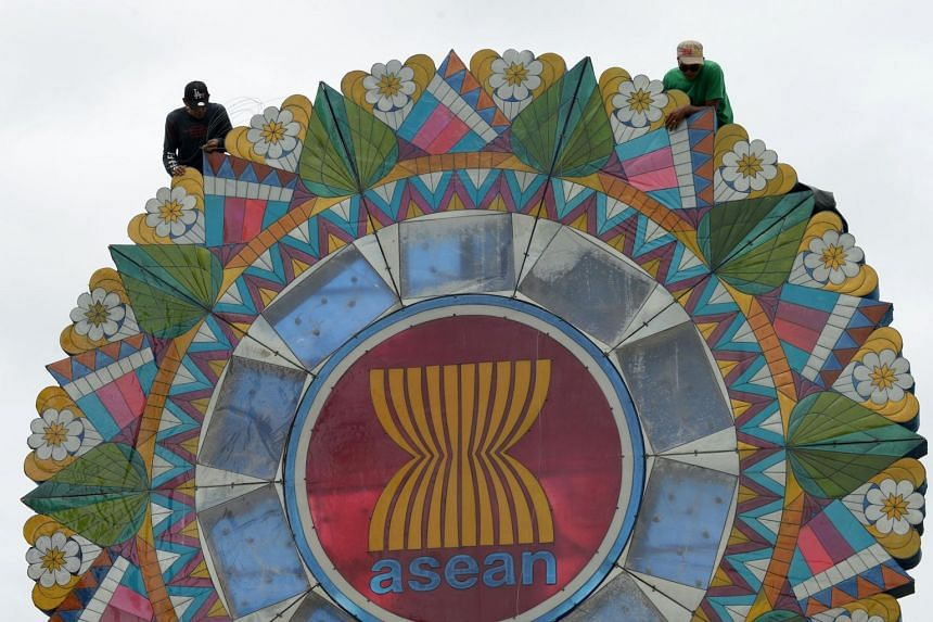 Labourers work on a giant lantern decorated with the logo for the Association of Southeast Asian Nations (ASEAN) displayed at the entrance to the venue of the ASEAN Regional Forum meeting in Manila on Aug 3, 2017.