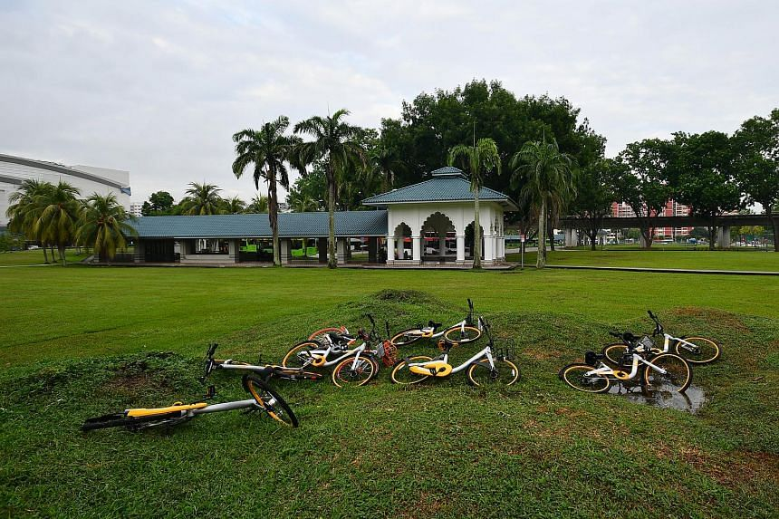 Bicycles from bike-sharing firms abandoned by users in a field near Pasir Ris bus interchange in May 2017.