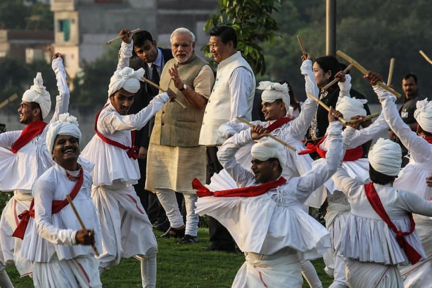 Indian Prime Minister Narendra Modi (centre left) escorts Chinese President Xi Jinping through a group of dancers in Ahmedabad, India, on Sept 17, 2014.