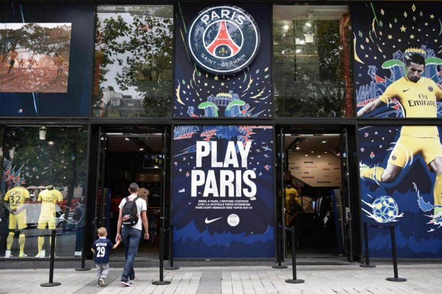 A man and a child enter the Paris-Saint-Germain (PSG) football club store on the Champs Elysees in Paris on Aug 3, 2017.