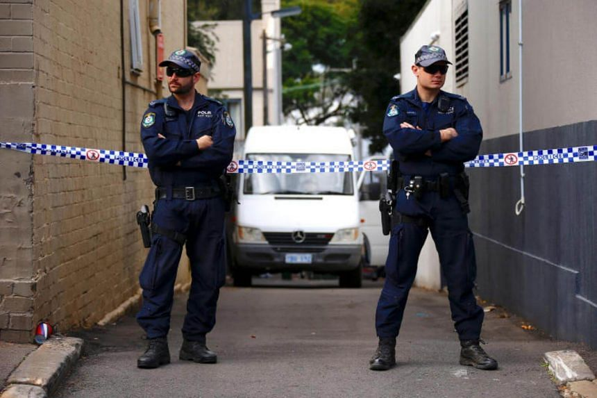 Police officers block a small alley where police vans are parked at a home being searched after Australian counter-terrorism police arrested four people in raids late on Saturday across several Sydney suburbs in Australia on July 30, 2017.