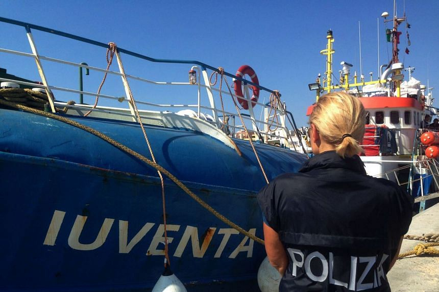 A police officer stands next to the Iuventa rescue ship in a police handout photo from Aug 2, 2017.