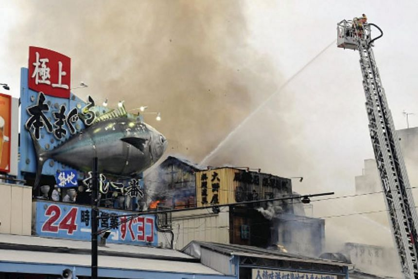 Firefighters battling a fire that broke out in Tokyo's Tsukiji fish market, on Aug 3, 2017.