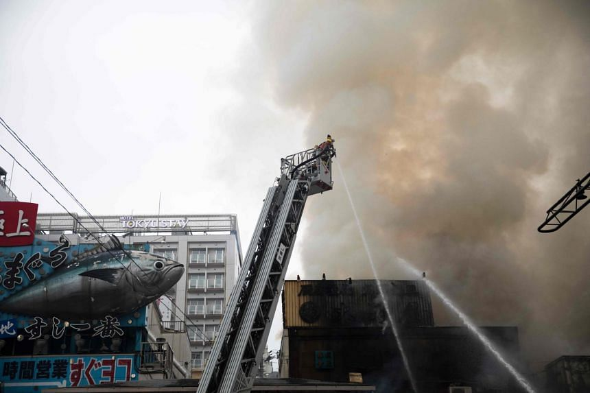 Japanese firefighters try to extinguish a fire at Tokyo's landmark Tsukiji fish market on Aug 3, 2017.