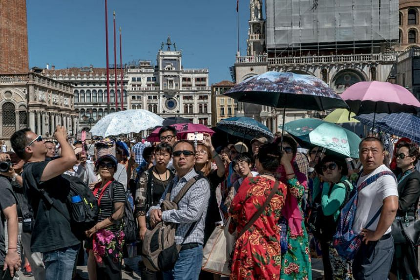 "Tourists in Piazza San Marco in Venice, Italy, on July 16, 2017. Italian officials worry that the famed, sinking city is being further swamped by a ""low-quality tourism"" that is making life almost unbearable for residents."