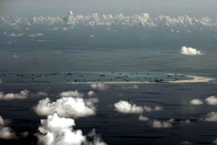 An aerial photo taken though a glass window of a Philippine military plane shows the alleged on-going land reclamation by China on Mischief Reef in the Spratly Islands.