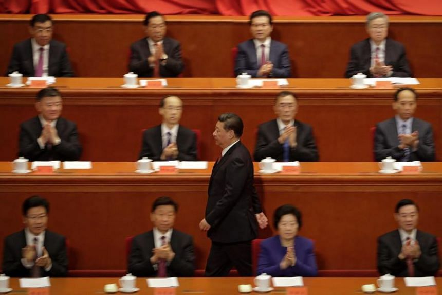 Delegates applaud as China's President Xi Jinping makes his way to the podium to deliver a speech at a ceremony to commemorate the 90th anniversary of the founding of the People's Liberation Army, at the Great Hall of the People in Beijing on August