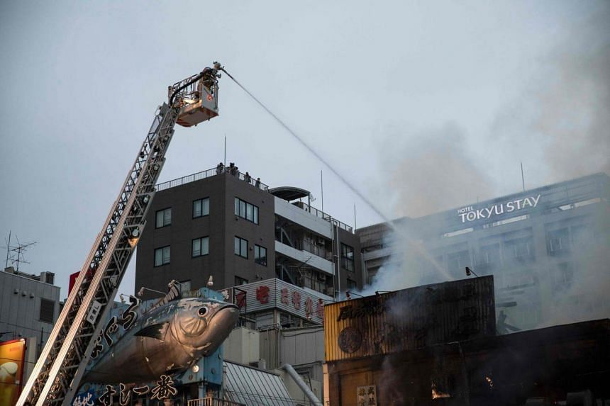 Japanese firefighters try to extinguish a fire at Tokyo's Tsukiji fish market on Aug 3, 2017.