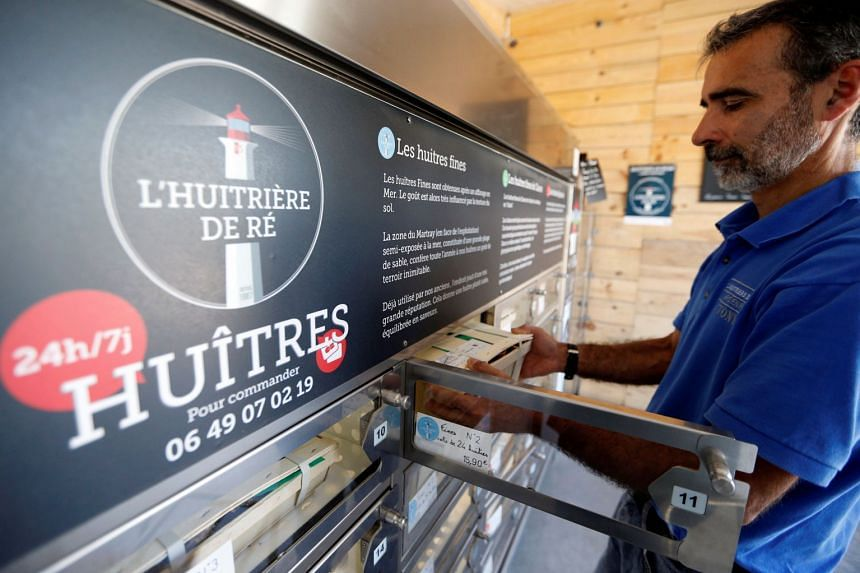 Aquaculturist Tony Berthelot installs oysters in an automatic oyster vending machine.