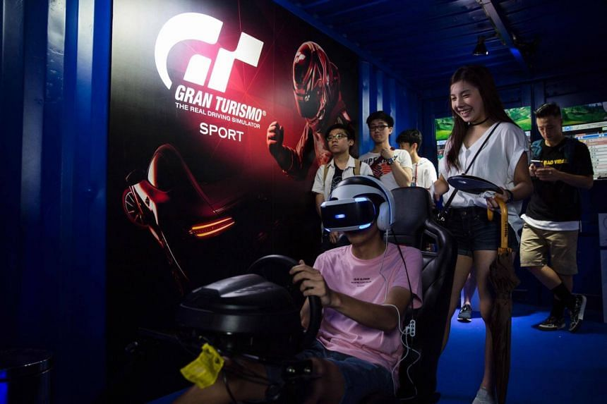 A gamer (centre) plays a driving console game during the eSports and Music Festival in Hong Kong on Aug 4, 2017.