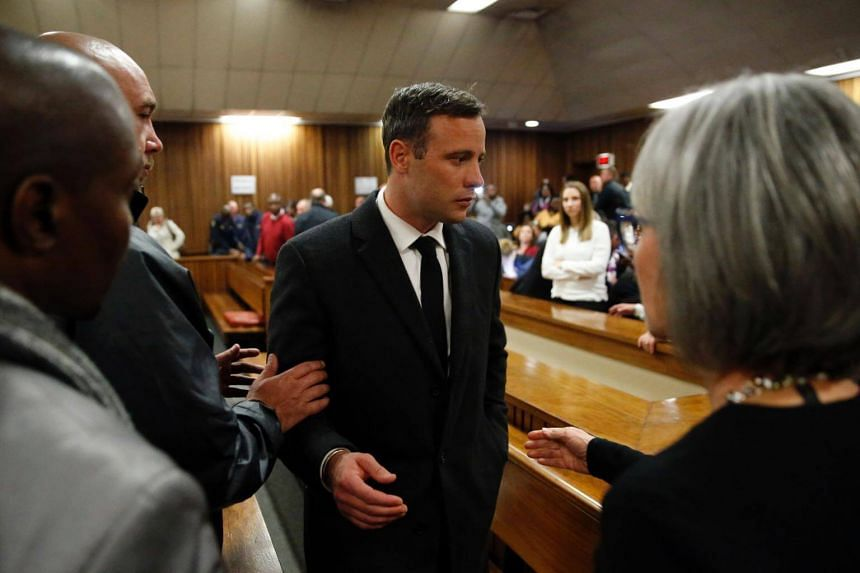 African Paralympian athlete Oscar Pistorius (centre) speaking with relatives as he leaves the High Court in Pretoria on July 06, 2016 after being sentenced to six years in jail for murdering his girlfriend Reeva Steenkamp three years ago.