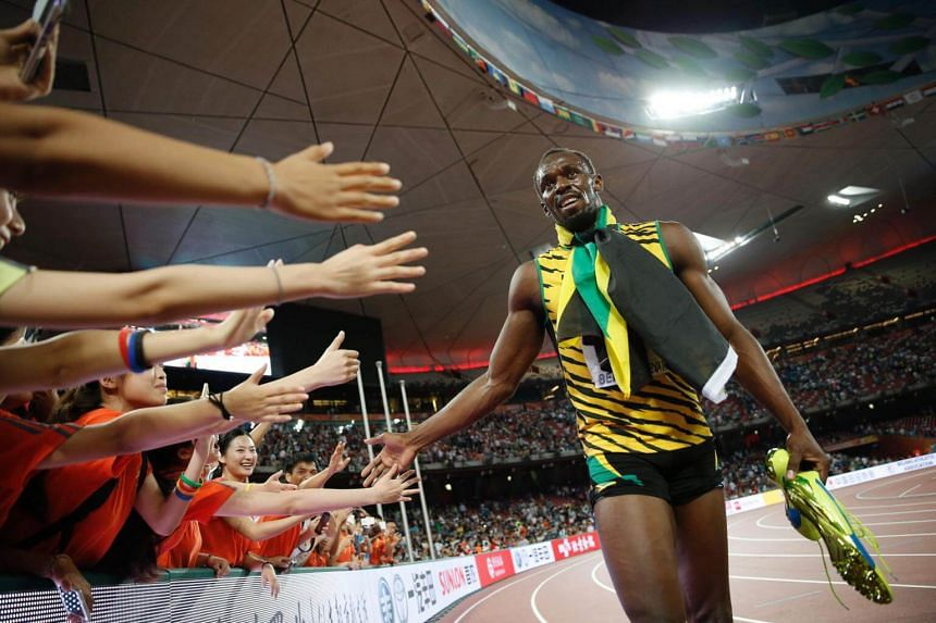 "Usain Bolt celebrating with fans after winning the final of the men's 200 metres athletics event at the 2015 IAAF World Championships at the ""Bird's Nest"" National Stadium in Beijing, on Aug 27, 2015."