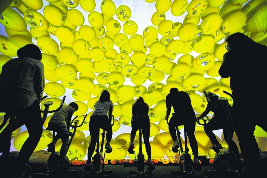 Cyclists on stationary bikes at Raffles City during CapitaLand Malls' Cyclo-moji-rama event yesterday. Featuring a 10m dome adorned with beaming emoji, participants cycled with the aid of a panoramic display that changed scenery as they pedalled. Cap
