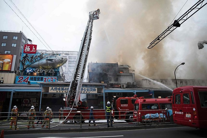 """Japanese firefighters trying to extinguish the fire at Tokyo's landmark Tsukiji fish market yesterday. The blaze was in Tsukiji's """"outer"""" market, and spread to five buildings covering some 300 sq m later in the evening. There were no immediate report"""