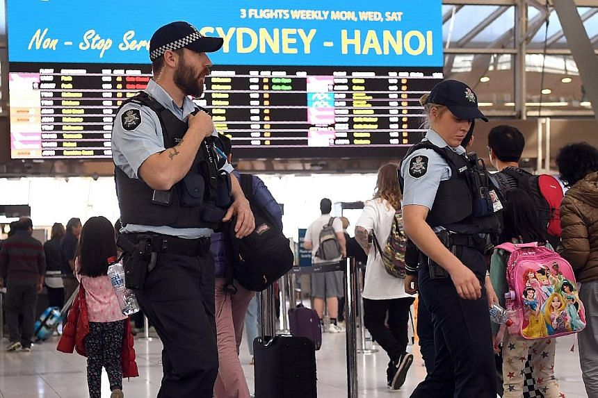 Police patrolling Sydney Airport last month. Experts have called for tighter security measures at Australian airports, including tougher screening of ground staff and identification checks for passengers.