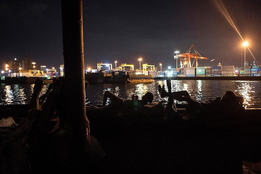 People kicking back amid activity going on in the port area of Manila Bay. Singapore firms have invested in port operations, ship-building and hotels in the Philippines.